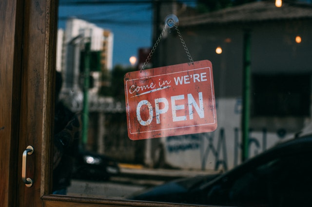 "A photo of a red sign that says ""Come in, We're Open"" on a glass door of a business."