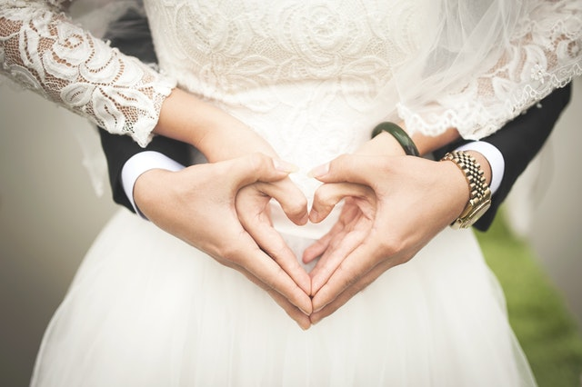 A close up of the midsection of a bride in a white wedding dress with the arms of a groom in a black suit wrapped around her. The bride's hands are being held by the groom's hands, forming a heart.